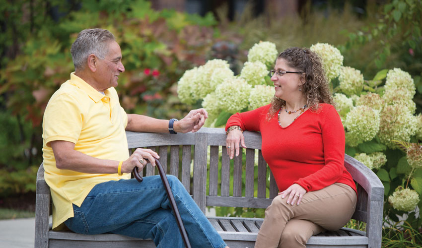 A senior man and younger woman talking together on a park bench