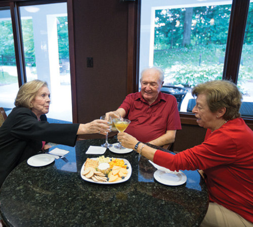A senior man and two senior women enjoying cocktails and an appetizer