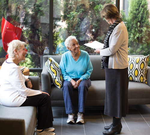 A well-dressed staffer talks to two senior residents, seated on gray couches in a Whitney Center common room