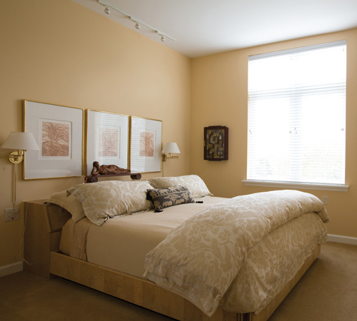A bedroom in one of Whitney Center's well-appointed apartment homes, featuring sconces, tasteful artwork and a window to allow natural light.