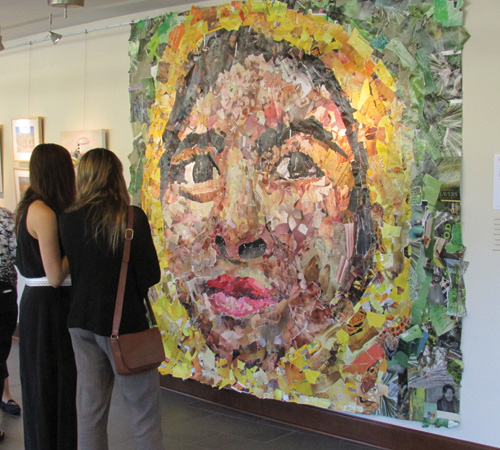 Two women observing a wall-sized mural of a face, made up of colorful decoupage