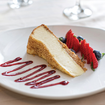 A slice of cheesecake and berries displayed on a white plate