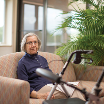 A senior woman relaxes on a sofa in a Whitney Center common room