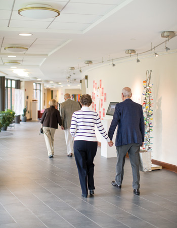 Two senior couples holding hands enjoy the works of art displayed in a Whitney Center hallway gallery