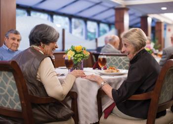Three seniors talking and having dinner together