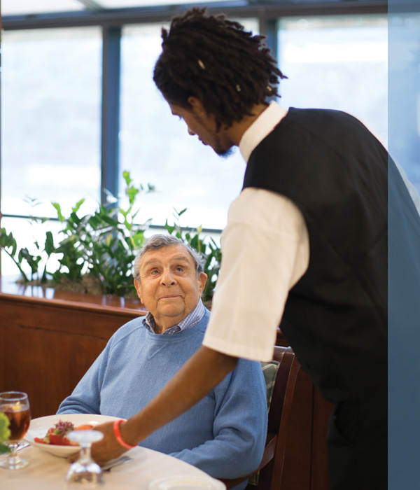 A young man serving dinner to a senior man in Whitney Center's Center Stage Restaurant