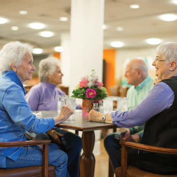 Three senior ladies and a senior man chat while sitting at a table in the Whitney Center Bistro