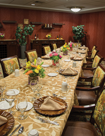 A long, formal dining room table, set for dinner