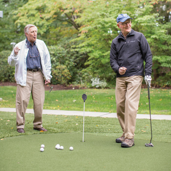 Two senior men in fall seasonal clothing practice putting on the Whitney Center putting green