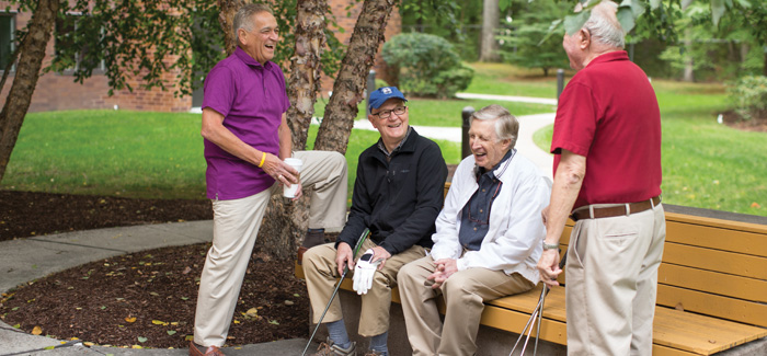 Four senior men holding golf clubs, gathered near a bench