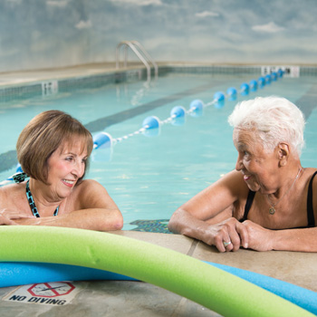 Two senior women relaxing in the water at the edge of a swimming pool