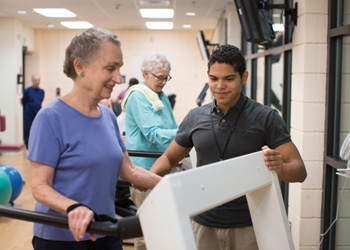 A young male staff member assists a smiling senior woman on the treadmill in the Whitney Center fitness center