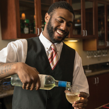 A friendly bartender smiles and pours a glass of white wine