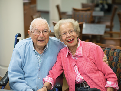 A smiling senior man and woman seated on a bench