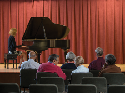 Six senior men and women sitting in Whitney Center's Cultural Arts Center, listening to a woman playing a grand piano