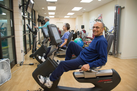 A senior man exercising on a Lifecycle at Whitney Center's state-of-the-art fitness center
