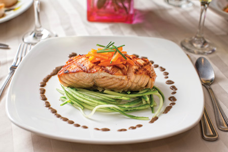 A white dinner plate with a salmon steak, garnished with carrots and greens