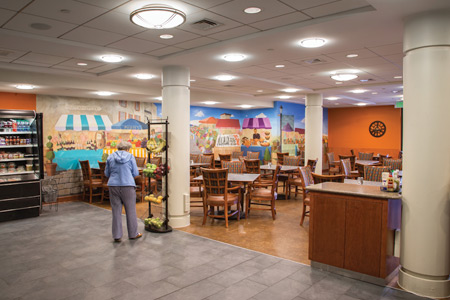 A senior woman picking out a piece of fruit at The Bistro, Whitney Center's casual and take-out dining cafeteria