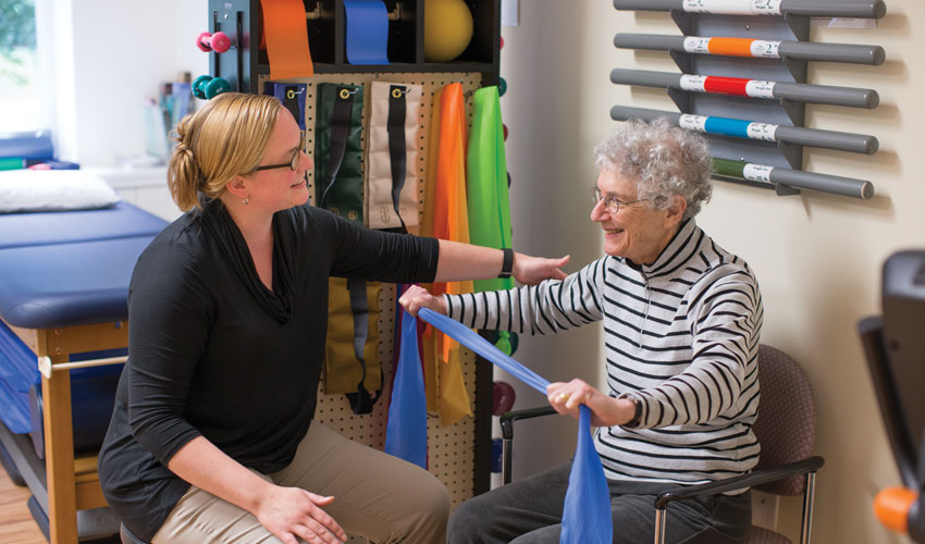 A female physical therapist working with a senior woman who is holding up a blue scarf