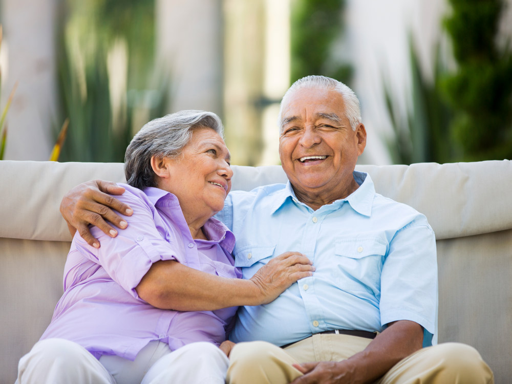 A well-dressed senior couple smile while posing for a photo