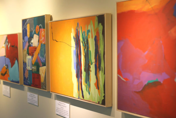 Four colorful framed art pieces displayed on a gallery wall