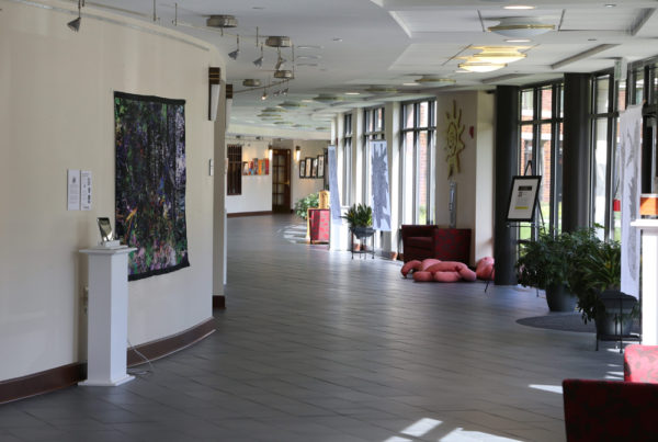 A hallway at Whitney Center, with works of art displayed on the walls, easels and pedestals