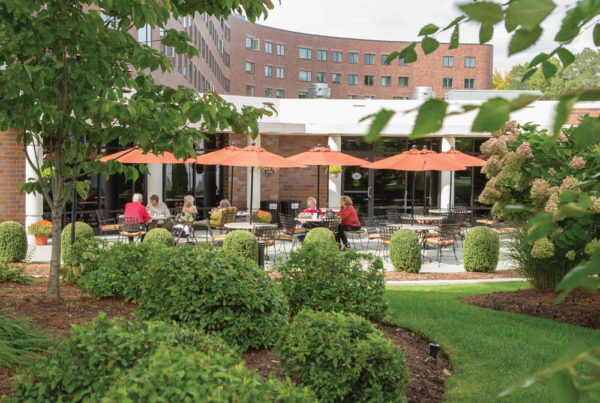 Several residents enjoying the outdoor patio terrace of Whitney Center