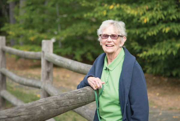 A smiling senior woman leans against a wooden railing on one of Whitney Center's on-campus walking trails