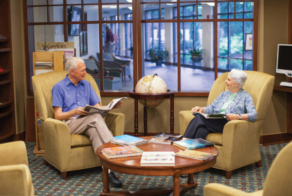 A smiling senior man and woman sitting in armchairs have a conversation in one of Whitney Center's common rooms