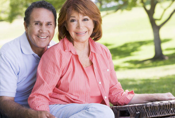 A senior couple with a picnic basket smile for a photo