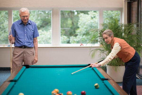 A senior couple playing billiards in a Whitney Center common room