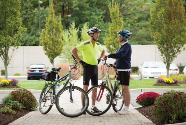 A senior man and woman dressed in bike gear, standing next to bikes and chatting