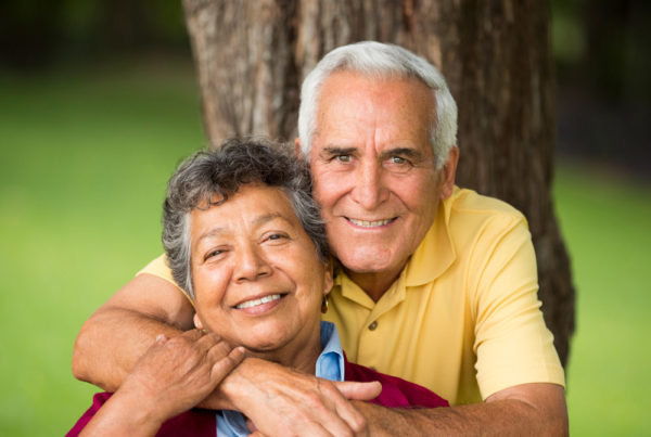 A senior couple smile and pose in front of a tree
