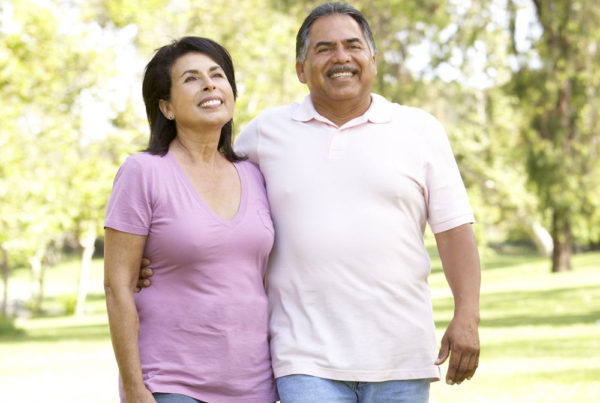 A middle-aged couple smile as they walk in a park-like setting on a summer day