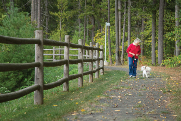 A senior woman walking a small dog on one of Whitney Center's nature trails