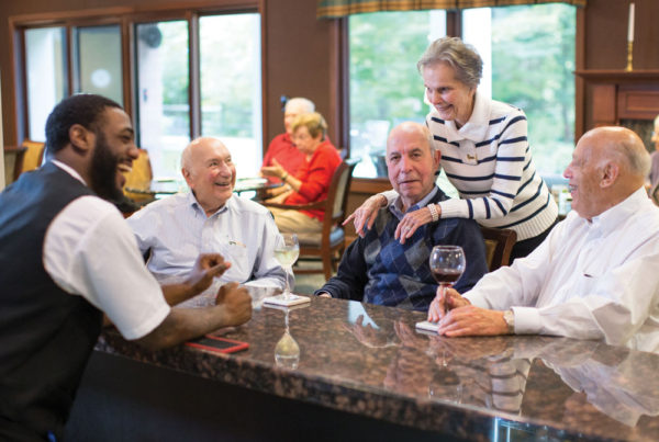 Four seniors gathered at a bar, having drinks and sharing a laugh with the bartender