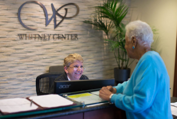 A staff member assists a resident at the front desk of Whitney Center