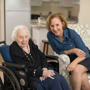 A senior woman with white hair smiles while visiting with a younger female loved one