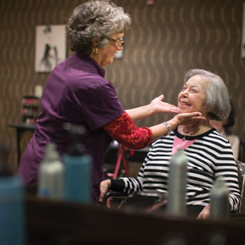 Female hair stylist touching up the hair of a senior woman