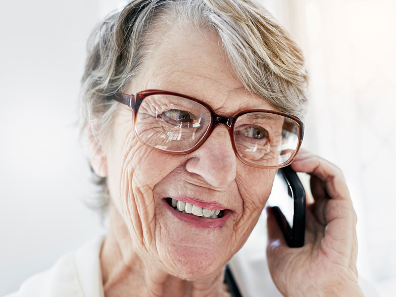 A senior woman wearing glasses, smiling as she talks on a cell phone