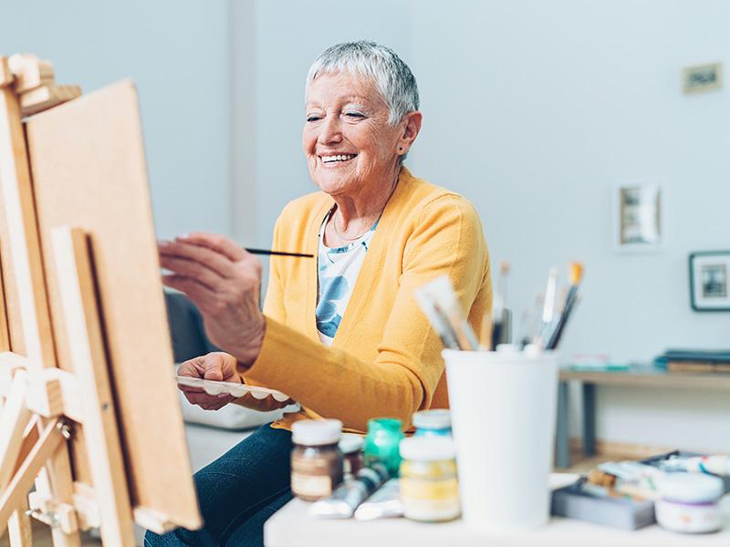 Senior artist woman drawing at home